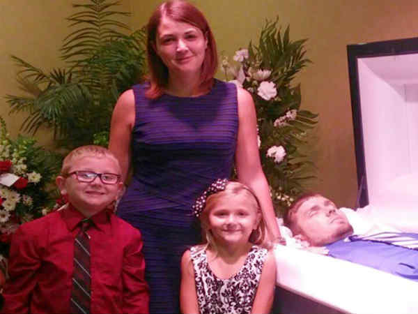 Woman poses with kids next to corpse of dead husband