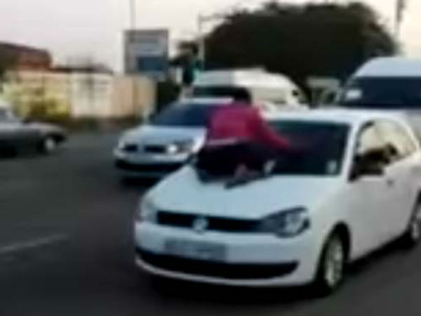 WATCH: Scorned wife clings to car bonnet as man drives away with 'mistress'