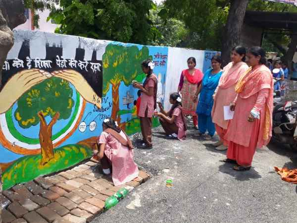 school kids draw messagefull paintings on the goverment wall in up