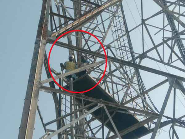 Two young men climb on the mobile tower in Shahjahanpur