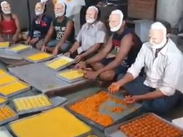 sweet shop workers Wearing a Modi mask during made sweet