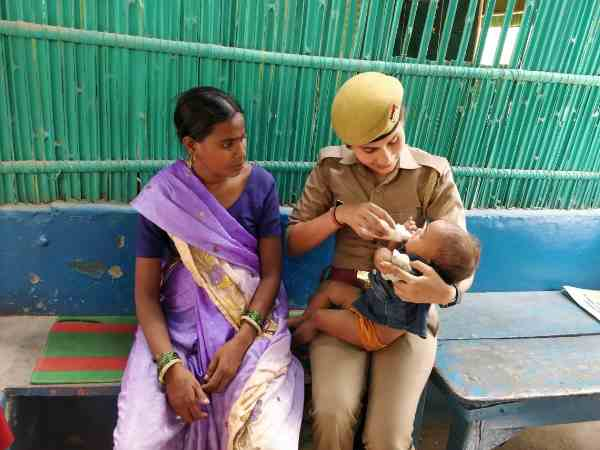 woman police constable feeding baby with milk on her lap
