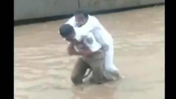 cop carried a sick man on his shoulders by making his way through a waterlogged route in Hyderabad
