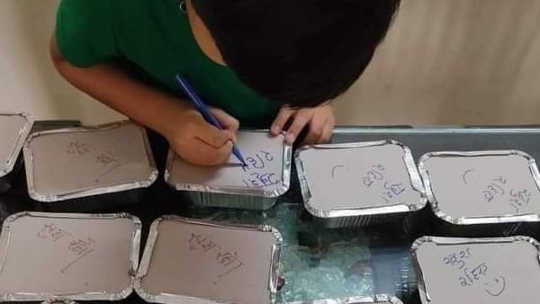त्रासदी के दौर में मुस्कान बिखेरती ये तस्वीर, मरीजों के लिए खाना पैक करती है मां, बच्चा लिखता है खुश रहिए