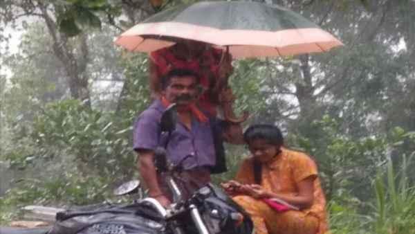 Father's day 2021:बेटी की ऑनलाइन पढ़ाई के लिए छाता लगाए घंटो बारिश में खड़ा रहा पिता, फोटो वायरल