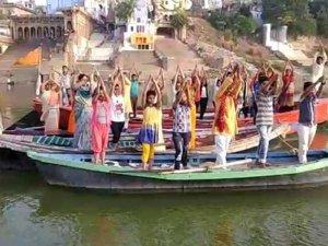 योग दिवस: गंगा की रेत और नाव पर लोगों ने किया योग