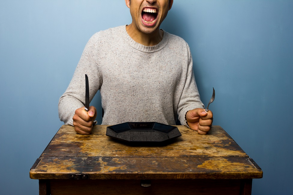Hungry man sits at a table with plate, knife and fork